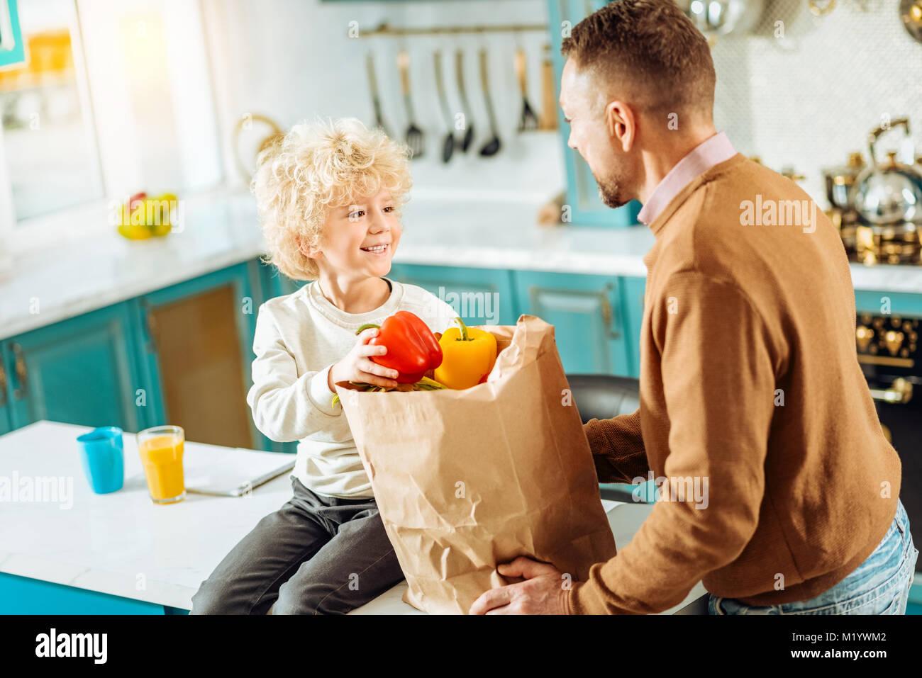 Joyful nice boy smiling to his father - Stock Image