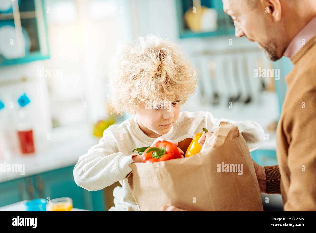 Cute curly boy looking into the bag - Stock Image
