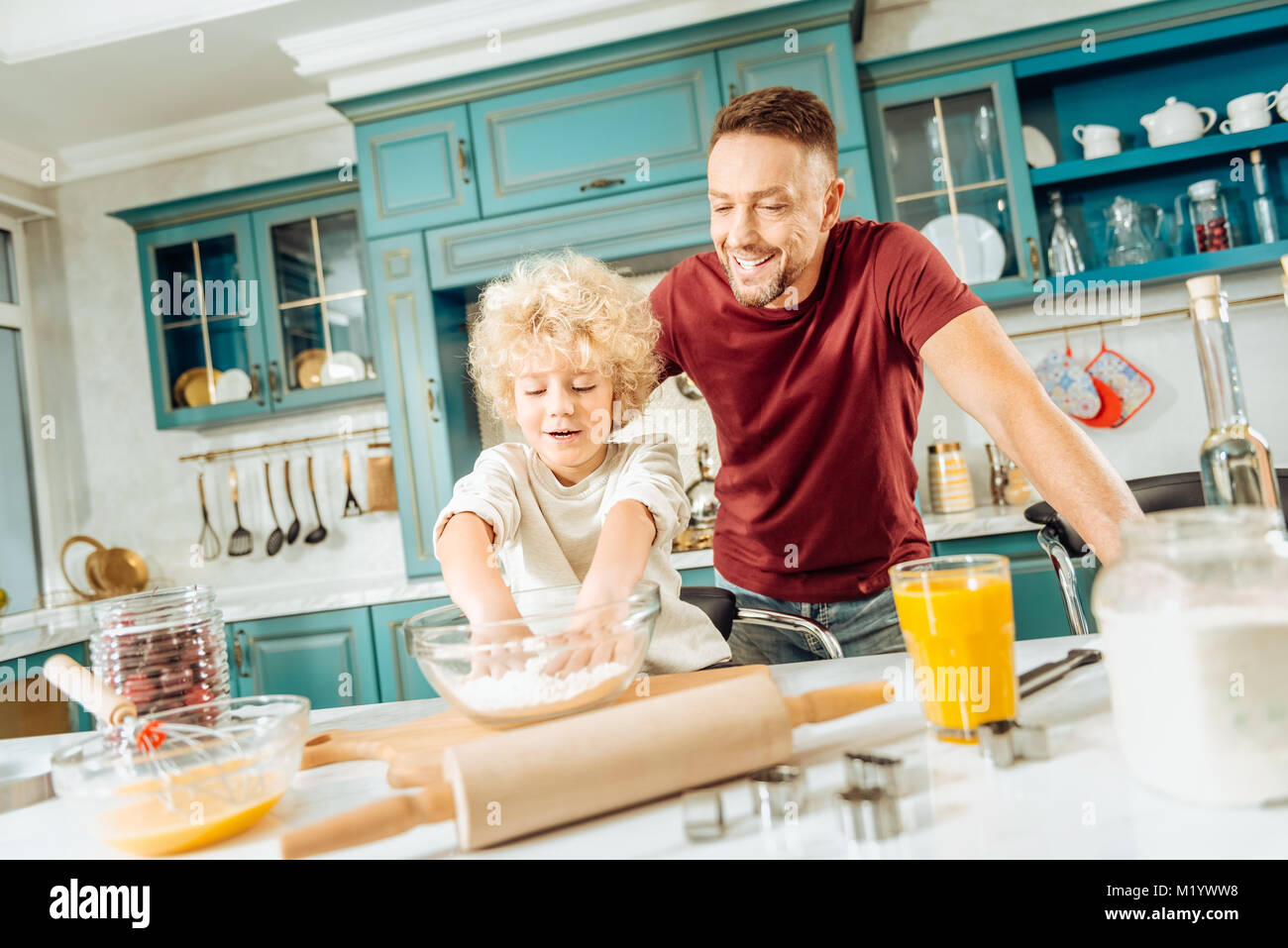 Nice delighted boy leaning to make dough - Stock Image