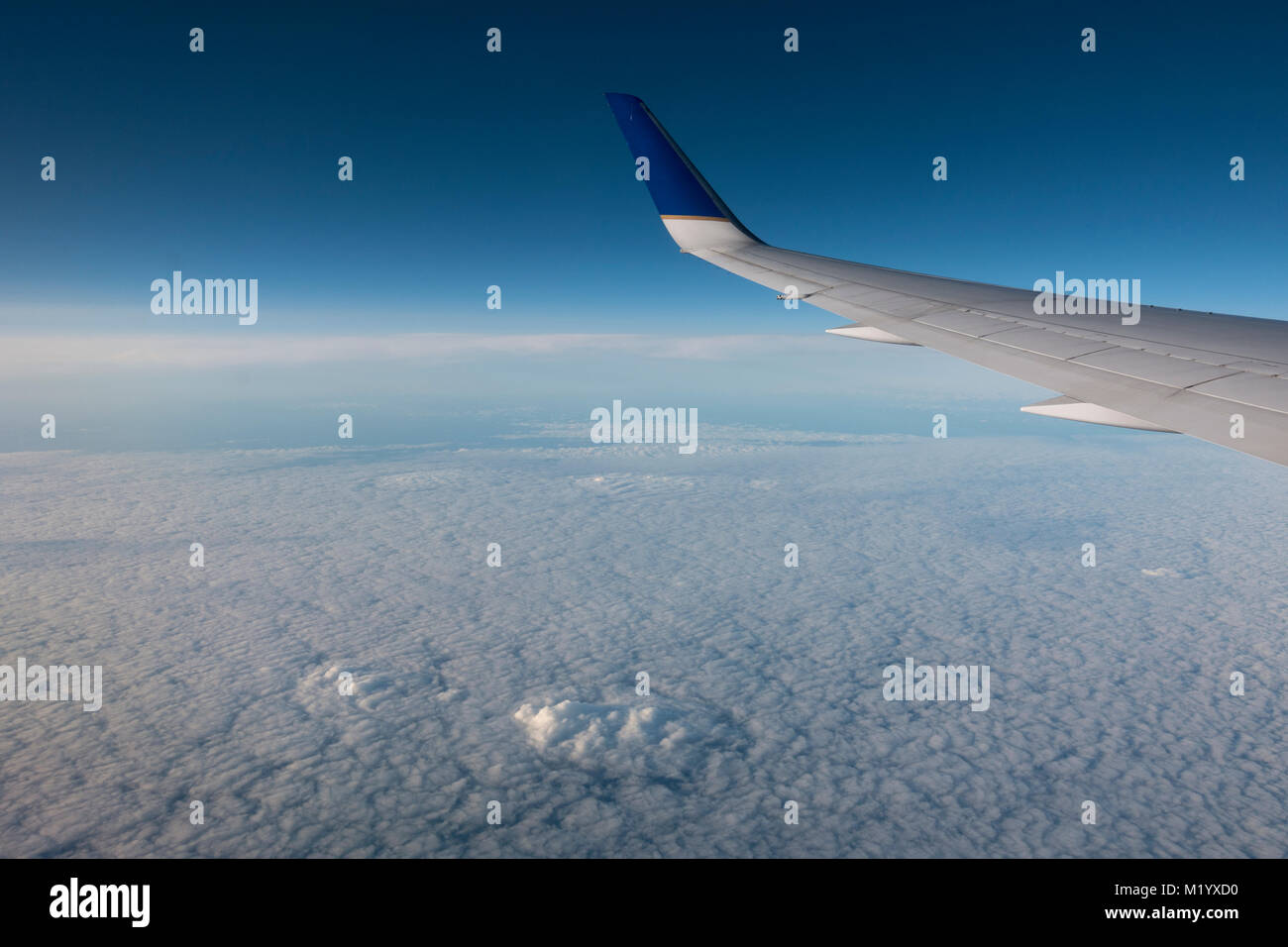 View out the window of a United passenger plane at the cloudy sky below. - Stock Image