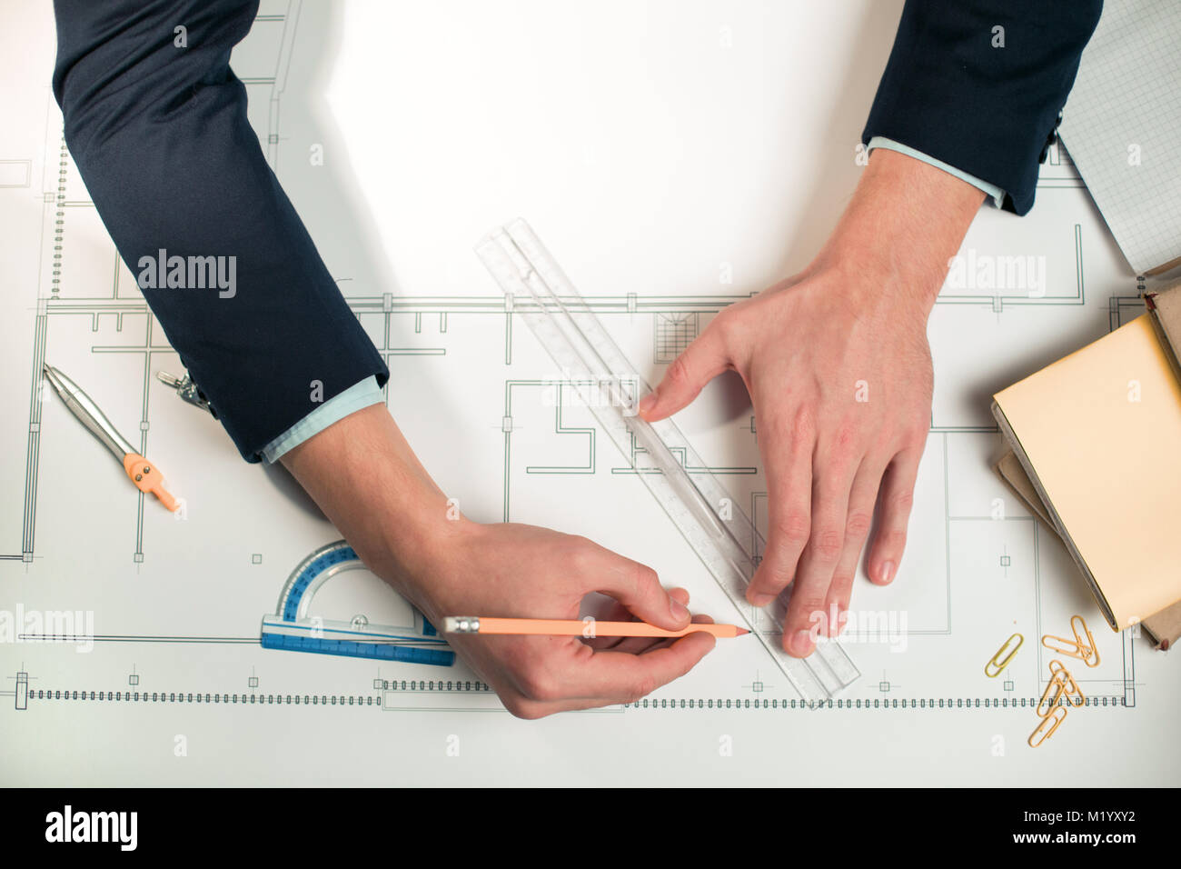 Young male hands sketching blueprint - Stock Image