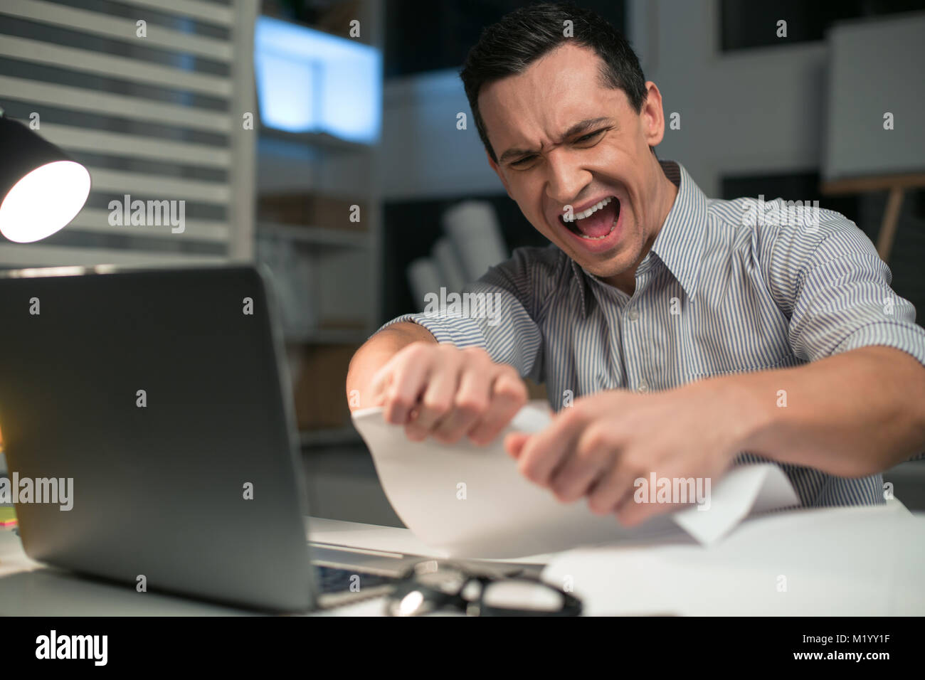 Emotional male employee tearing papers - Stock Image