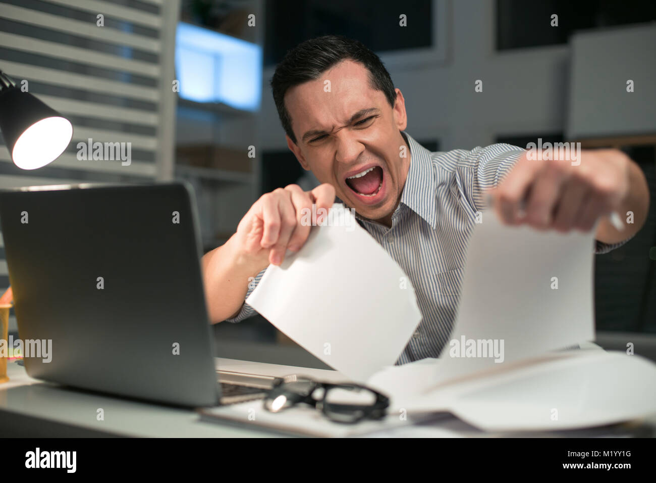 Attractive male employee rending papers - Stock Image