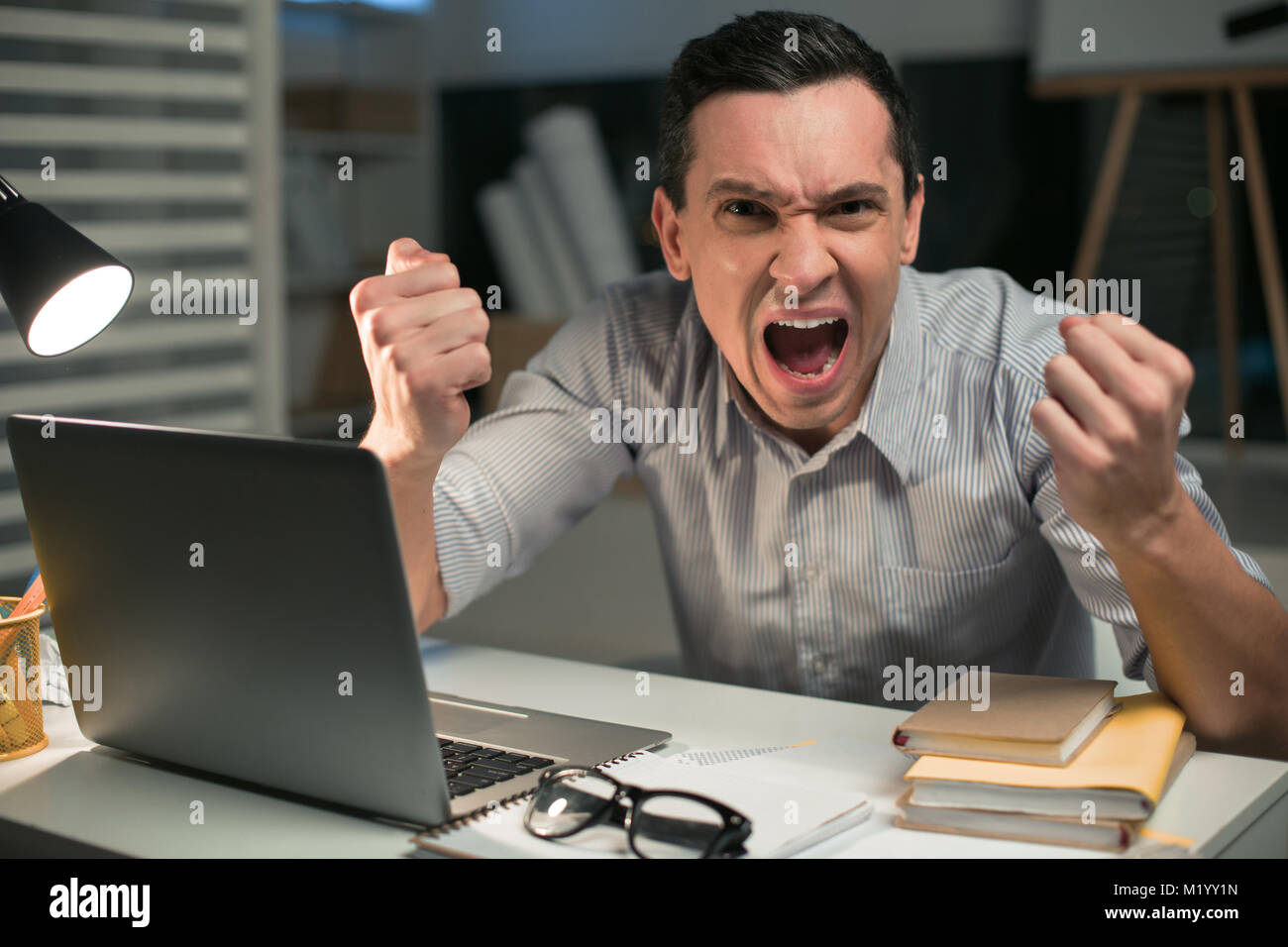 Mad male employee overloading with work - Stock Image