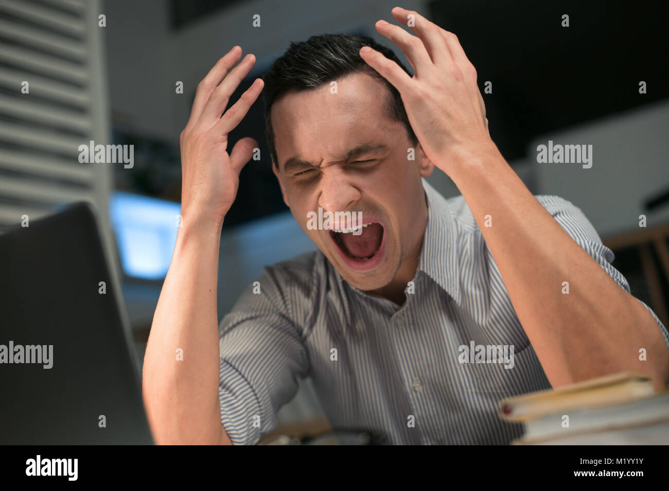 Pretty male employee going crazy - Stock Image