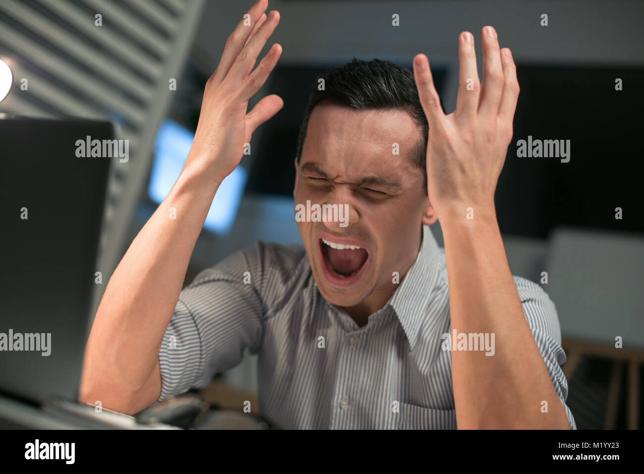 Emotional male employee loosing his mind - Stock Image