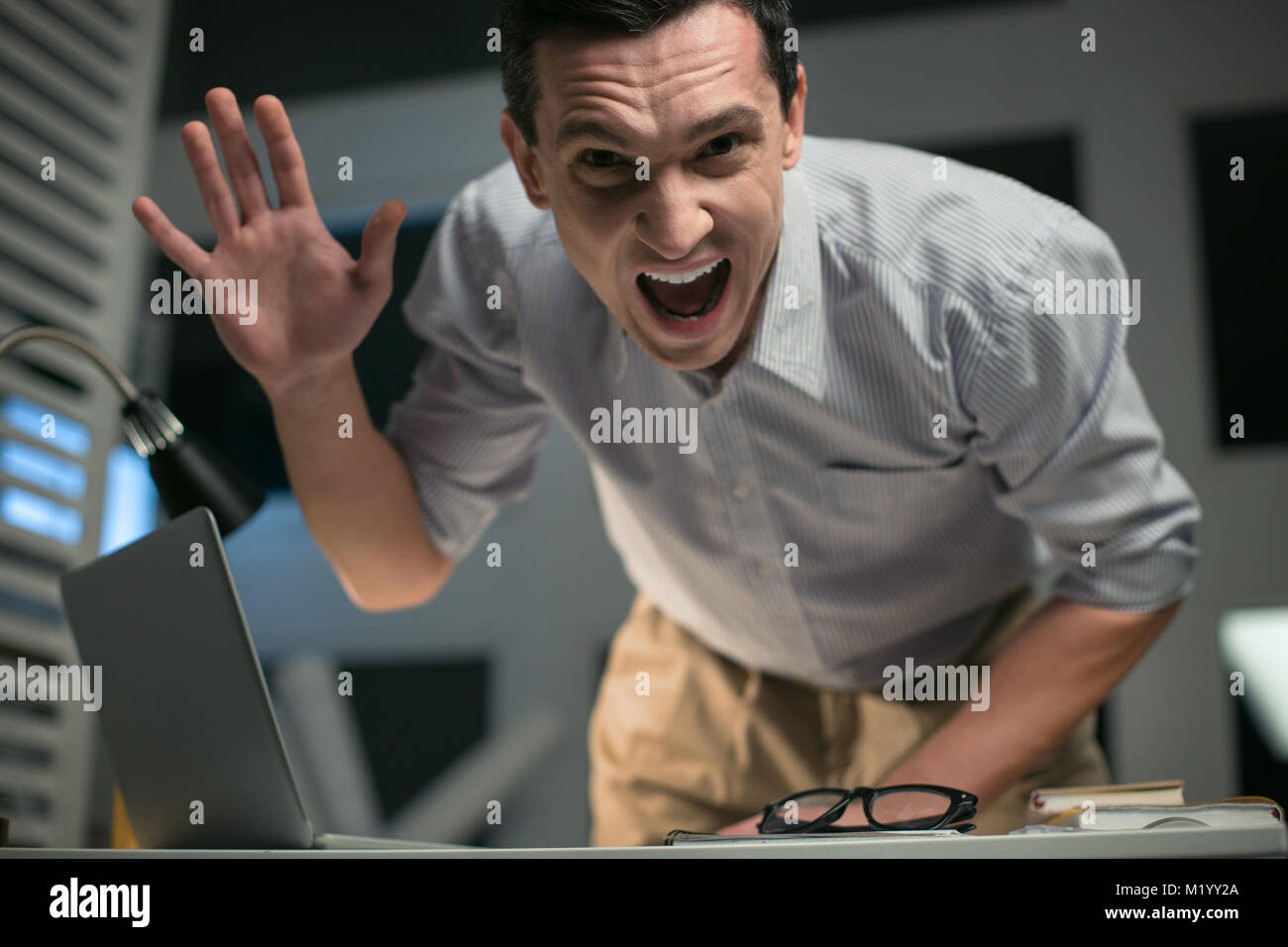 Mad male employee showing aggression - Stock Image