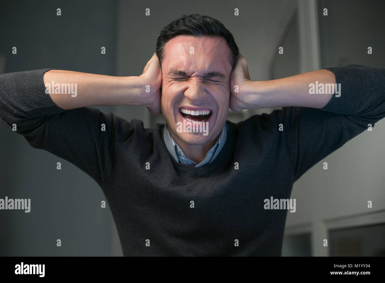 Desperate young man yelling loudly - Stock Image