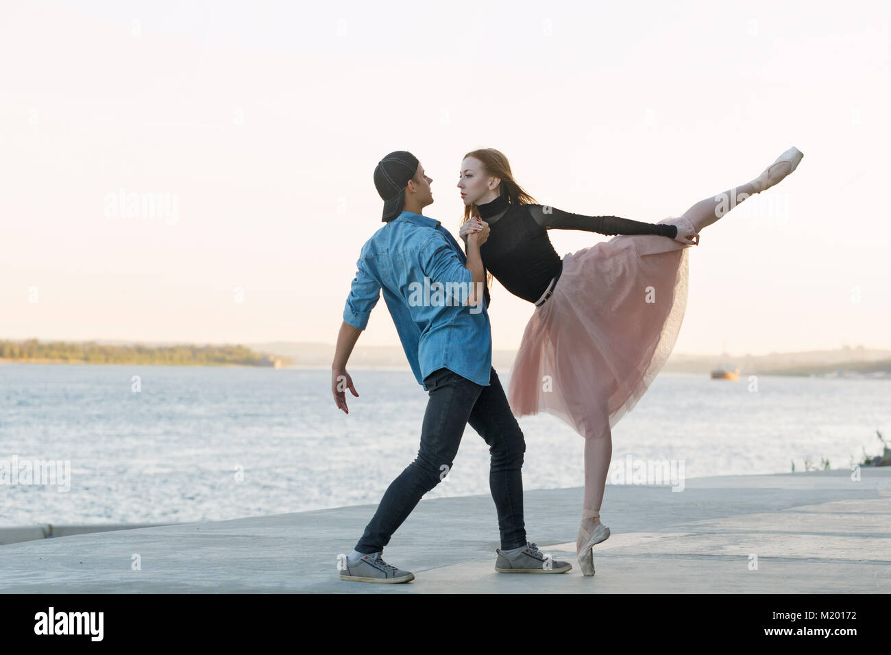 A young couple in love passionately dances on the embankment of the city. Dancer and sportsman Parkour. Date of Stock Photo