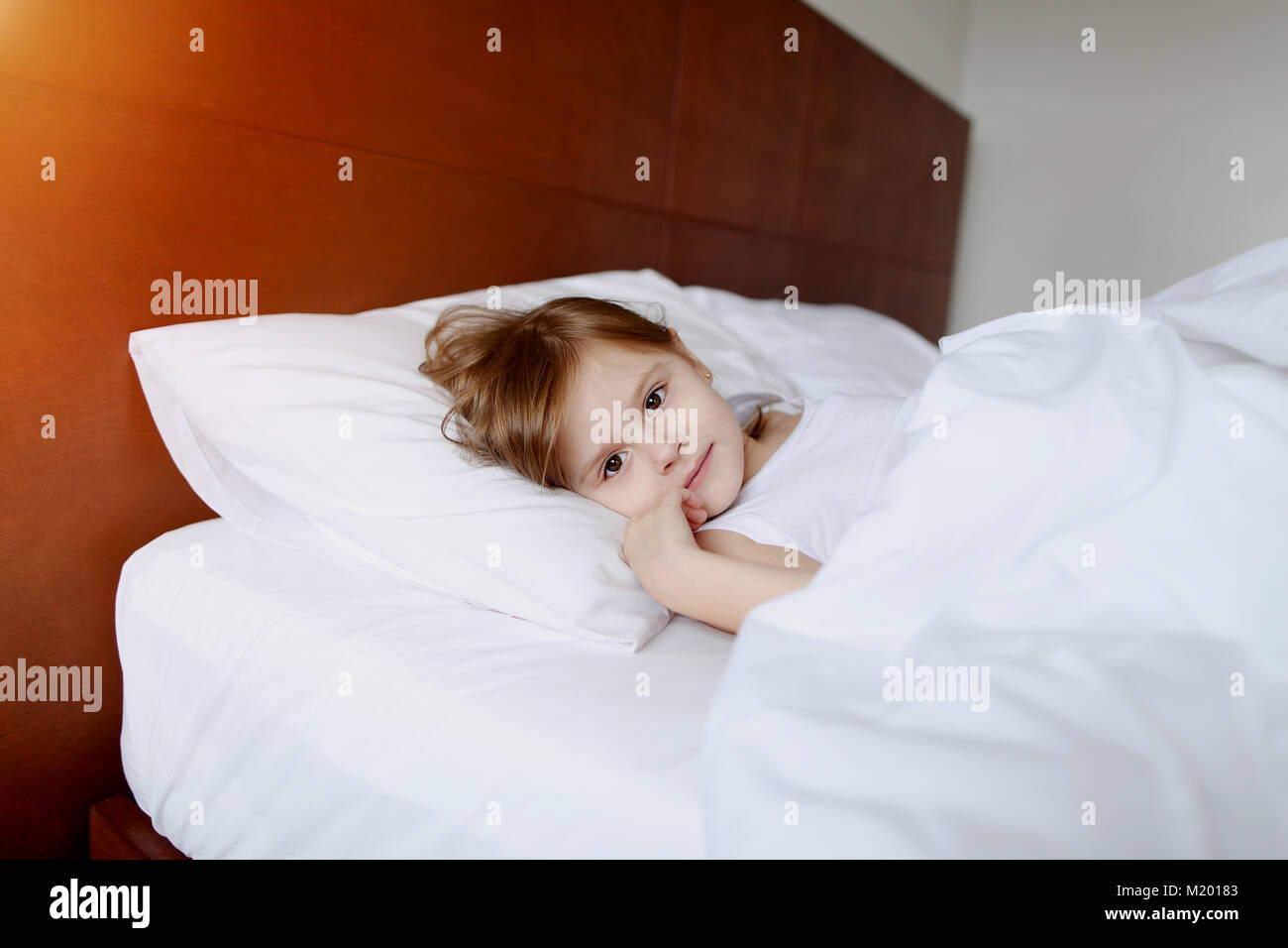 portrait of little daughter smile laying at white bed home on sunny good morning - Stock Image