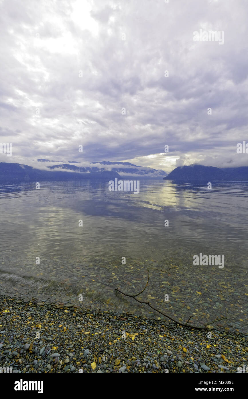 Clean clear water of lake Teletskoye. The wave incident on the beach Stock Photo