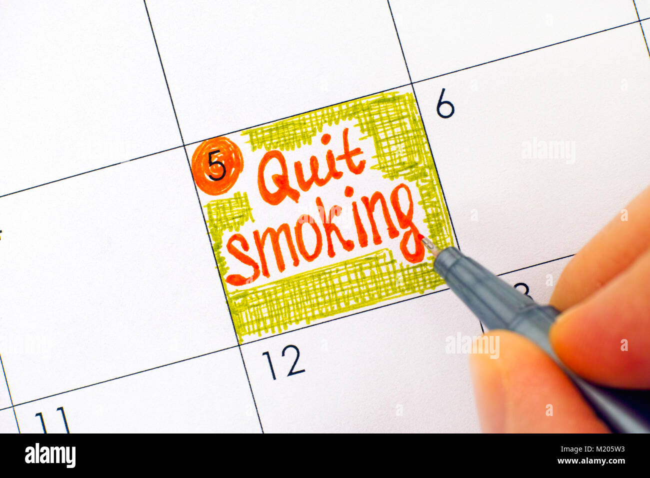 Woman fingers with pen writing reminder Quit Smoking in calendar. Close-up. - Stock Image