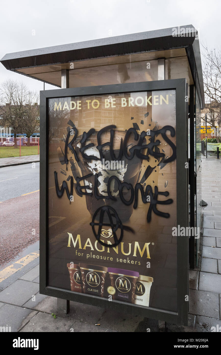 'Refugees Welcome' spray painted on a bus shelter by London anarchists in Deptford, south east London, UK. - Stock Image