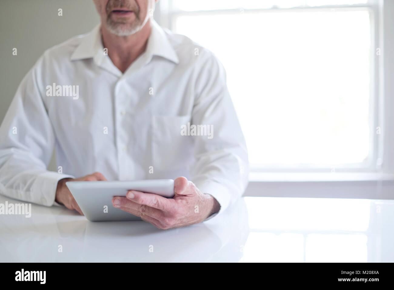 Senior man using digital tablet. - Stock Image