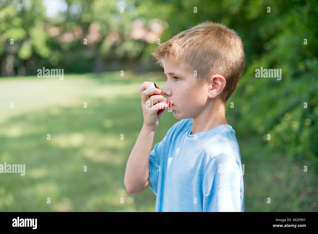 Young boy using an inhaler. - Stock Image
