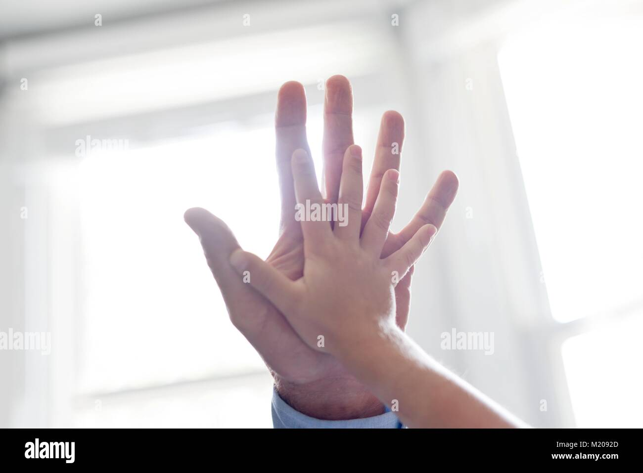 Child and adult touching hands. - Stock Image
