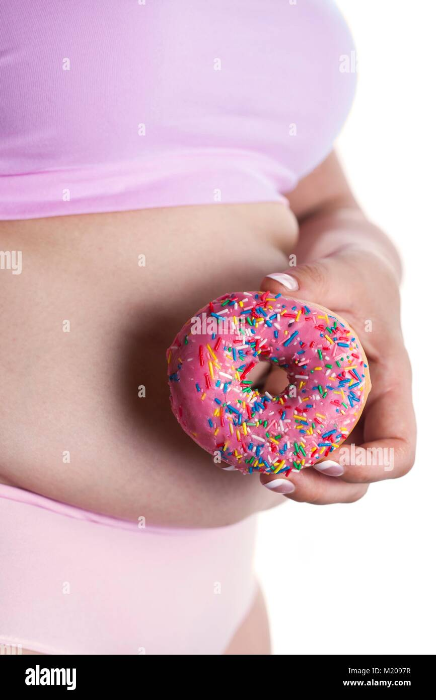 MODEL RELEASED. Woman holding doughnut in front of belly. - Stock Image