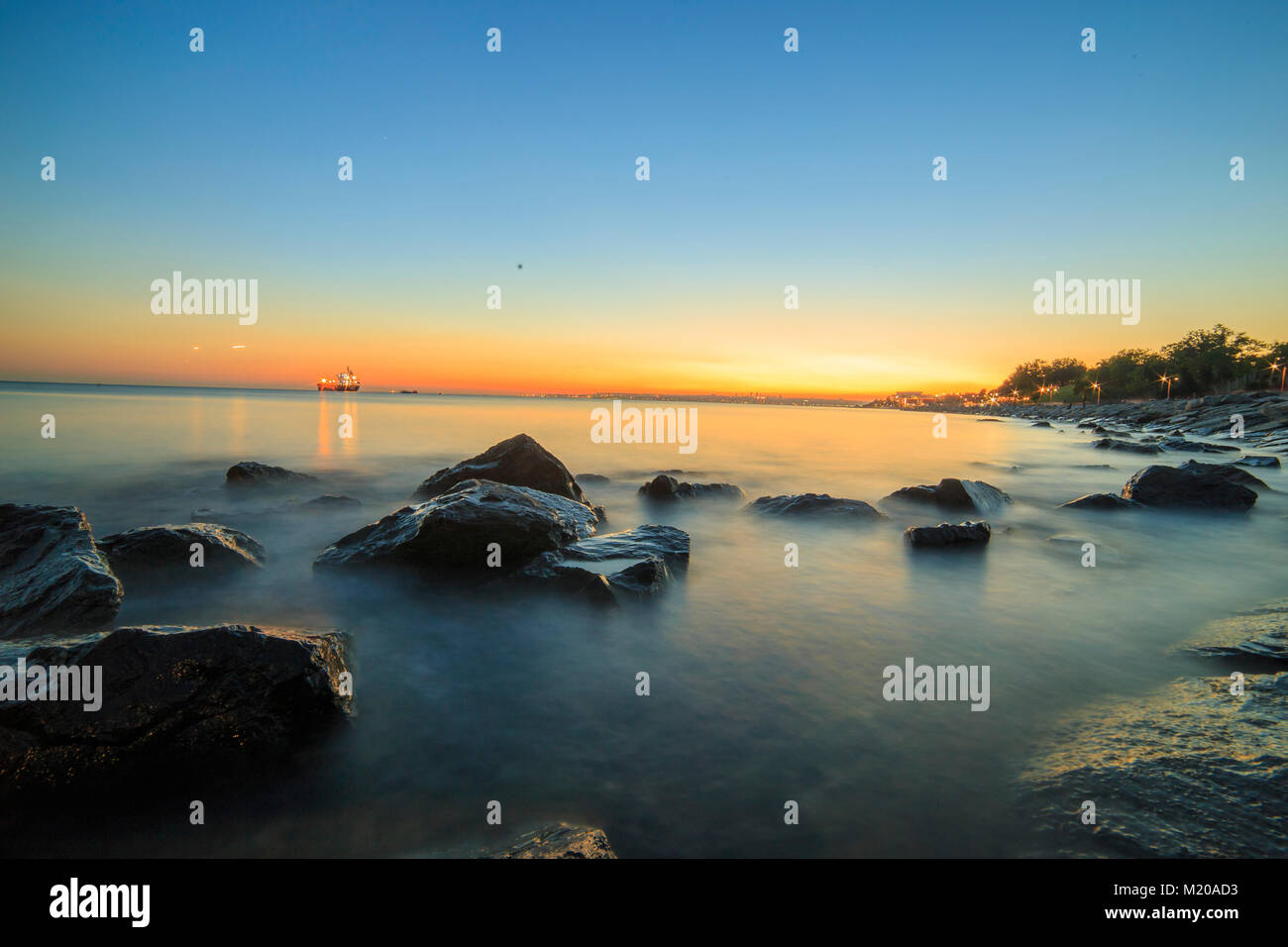 Empty sea and rocks During the sunset with Silky Sea beacuse of the long exposure via ND Filter image for design - Stock Image