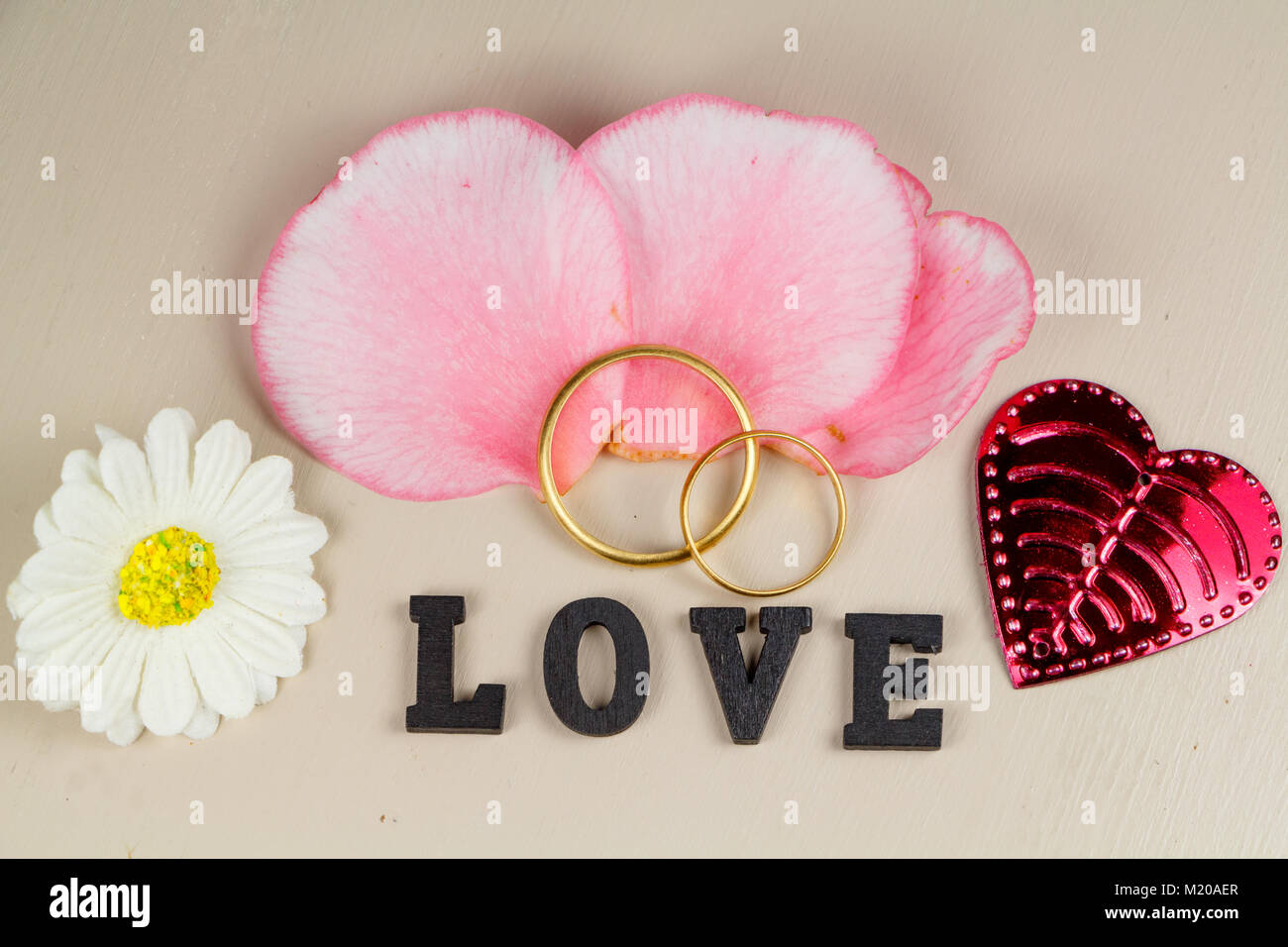 Two wedding rings made in gold, pink petals, pink heart, white ...