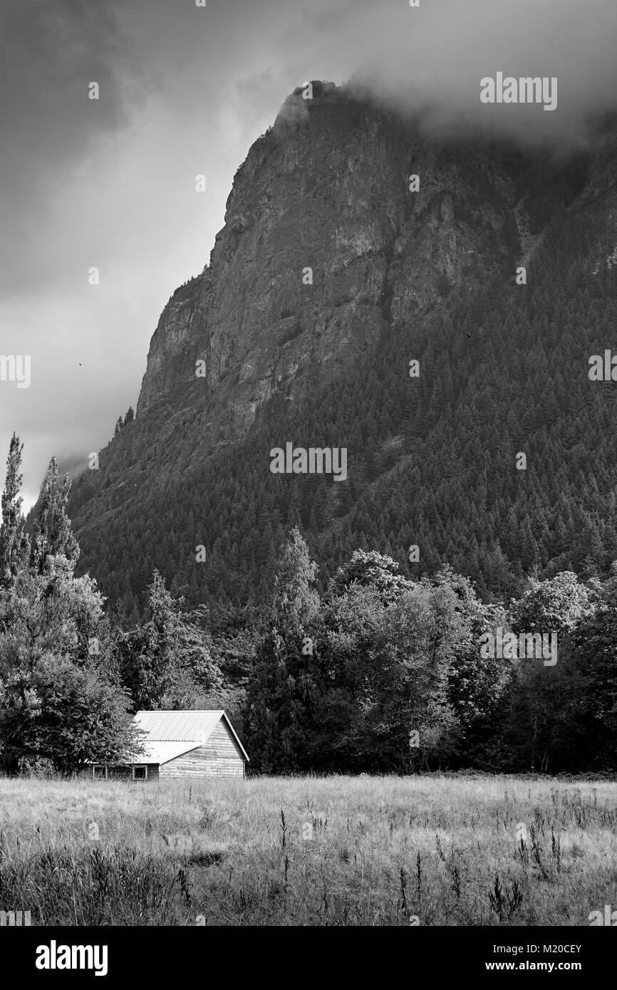 black and white image of a farm building cast against a clound covered mountain in the background - Stock Image