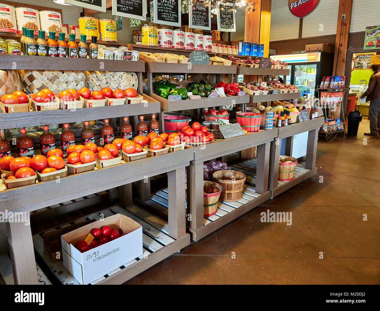 Display shelves in local fresh produce specialty market with organic fruits and vegetables and specialty food in - Stock Image
