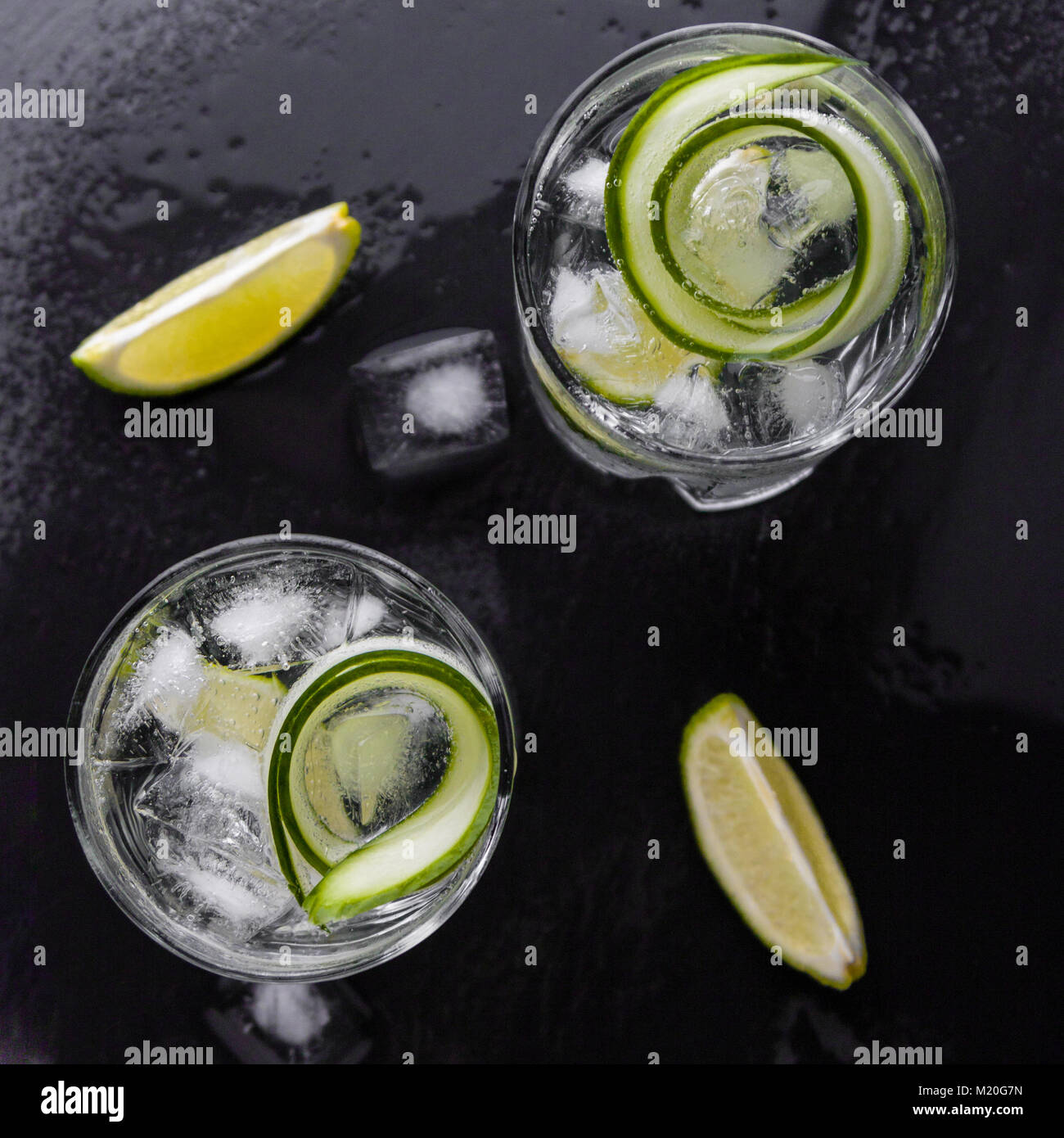 gin tonic with cucumber, lime and ice in glass - Stock Image