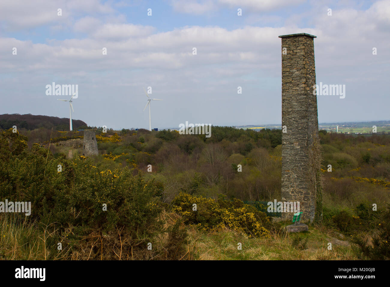 An old industrial chimney stack with modern wind turbines in the background at the old lead mines site at Whitespots Stock Photo