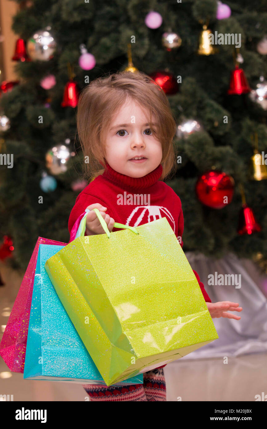 bf0b4a2bc portrait of a pretty little girl in a red sweater with gifts at the ...