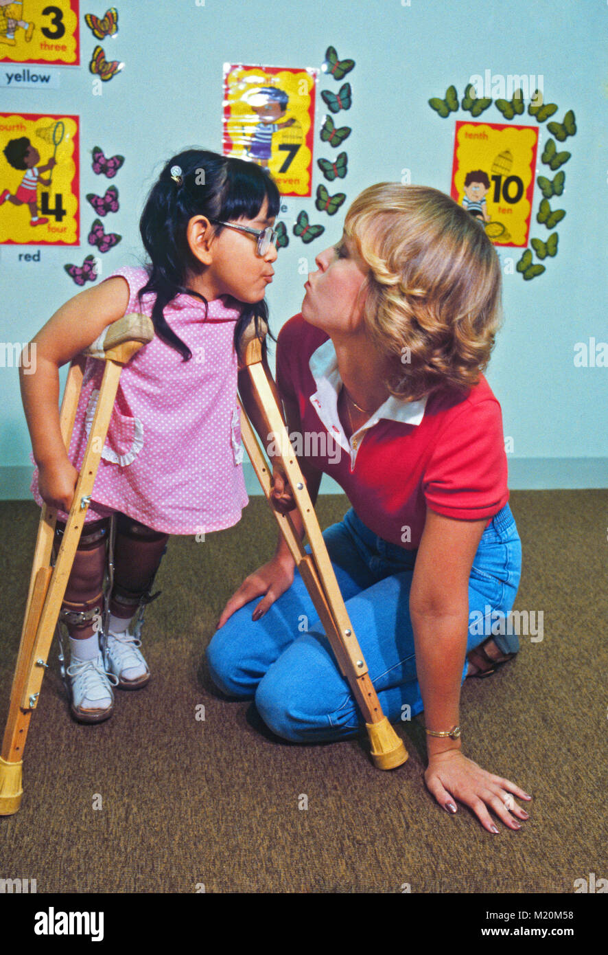 A seven year old crippled Hispanic child being cared for by a playful care-giver/nurse at a children's hospital - Stock Image