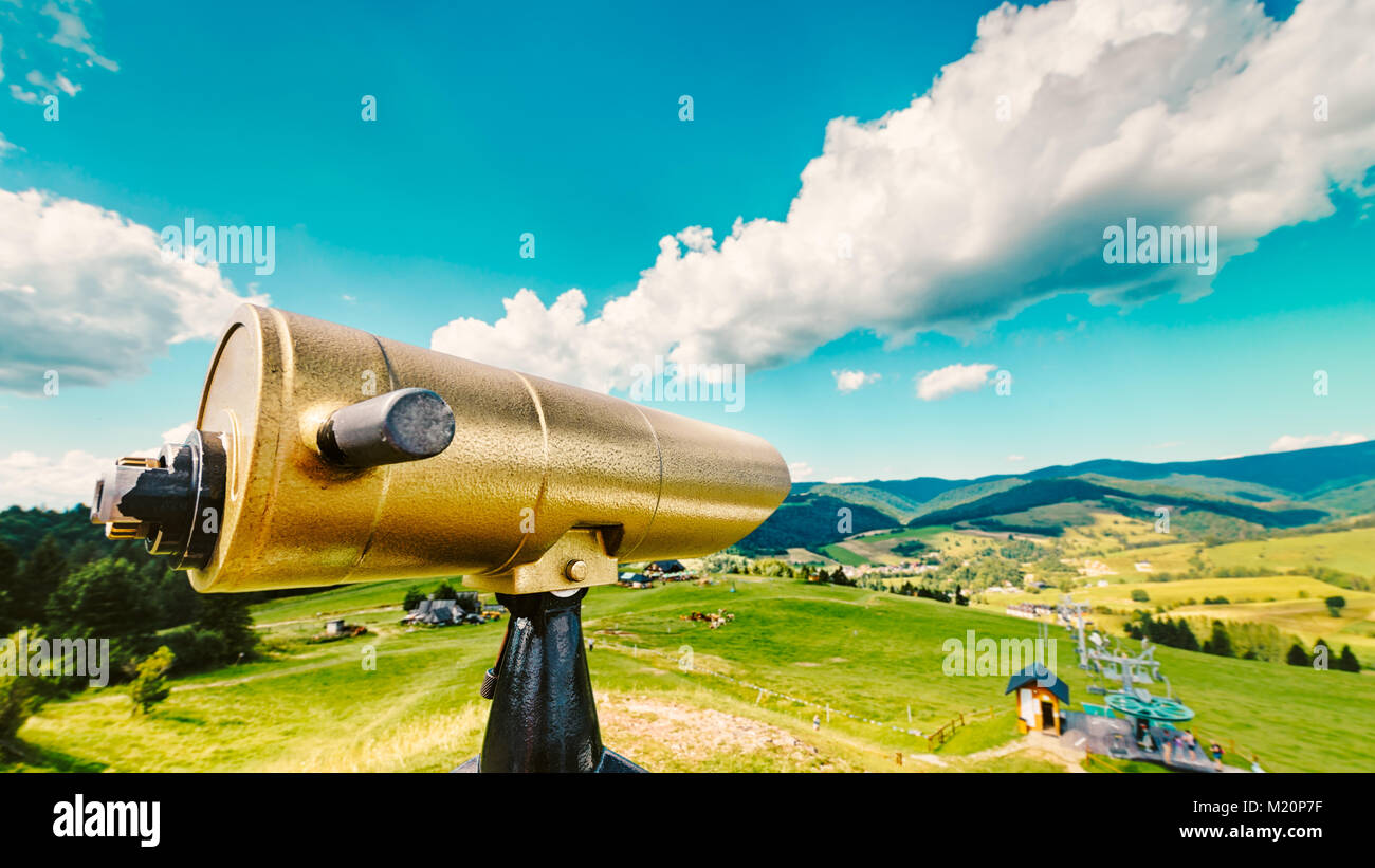 Golden tourist telescope and blurred Pieniny mountains landscape in the background - Stock Image