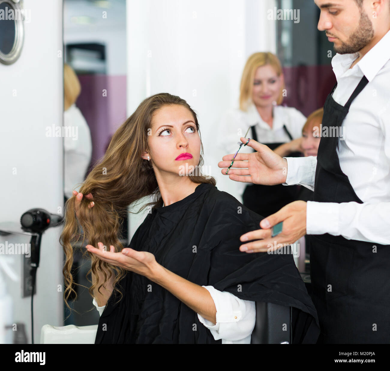 Hairdresser dispute with the female client in the barbershop - Stock Image