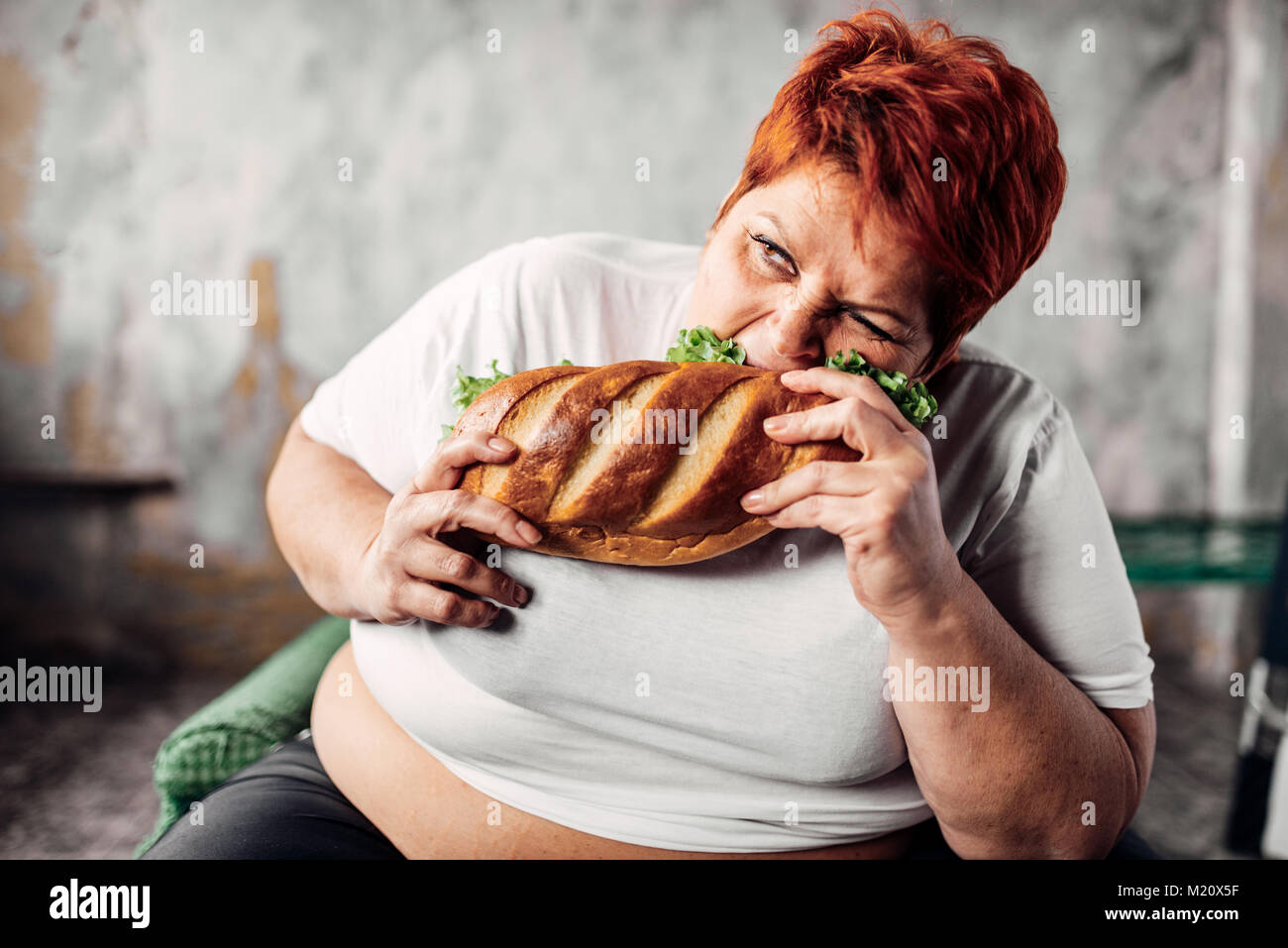 Fat woman eats sandwich, overweight and bulimic. Unhealthy lifestyle. Obesity - Stock Image