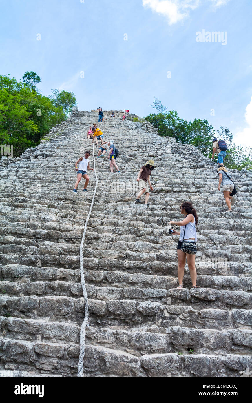 tourists climbing on pyramid Coba Mexico - Stock Image