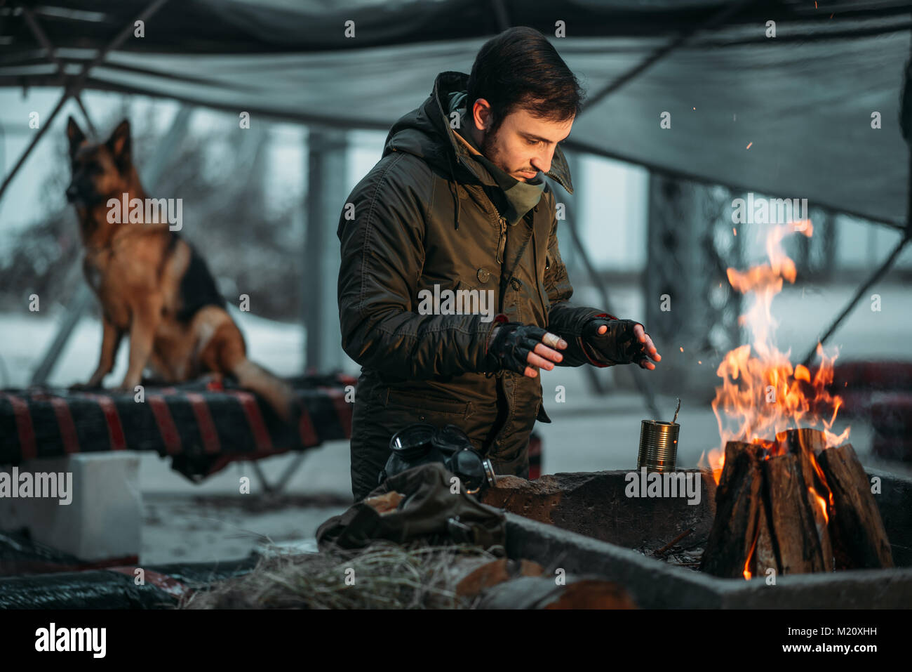 Stalker warms his hands on fire, dog on background. Post apocalyptic lifestyle on ruins, doomsday, judgment day - Stock Image