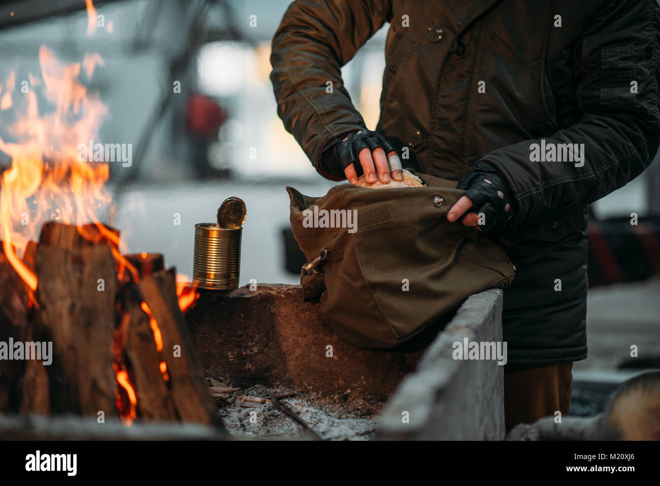 Stalker, male person warms his hands on fire. Post apocalyptic lifestyle with gas mask, doomsday, - Stock Image
