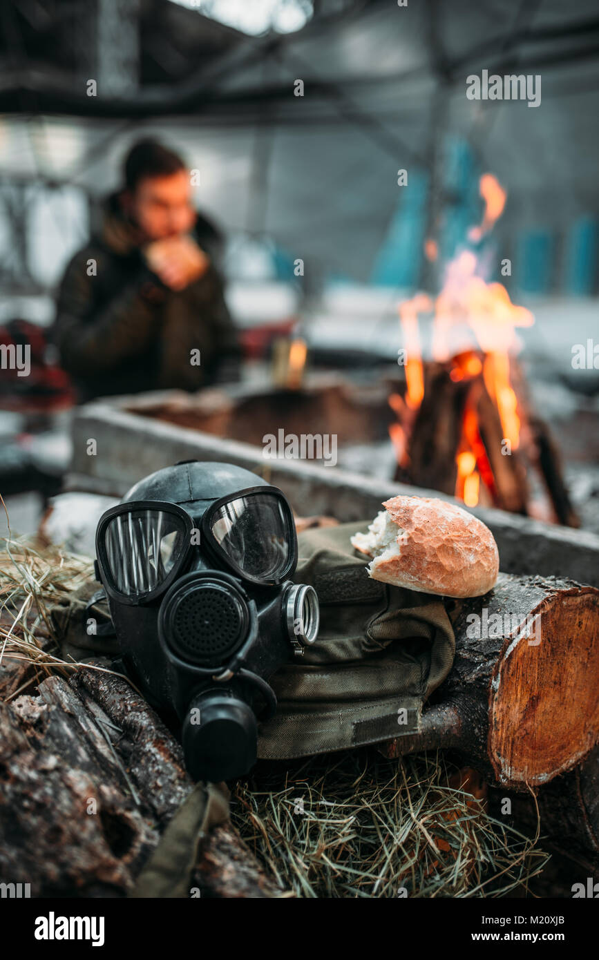 Gas mask against fire, stalker eats on background. Post apocalyptic lifestyle, doomsday, horror of nuclear war - Stock Image