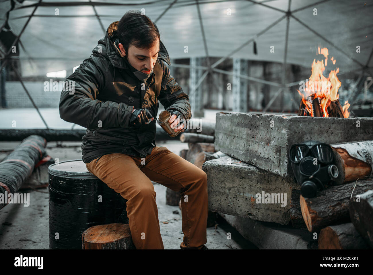 Stalker, male person eating against fireplace. Post apocalyptic lifestyle, doomsday, horror of nuclear war Stock Photo