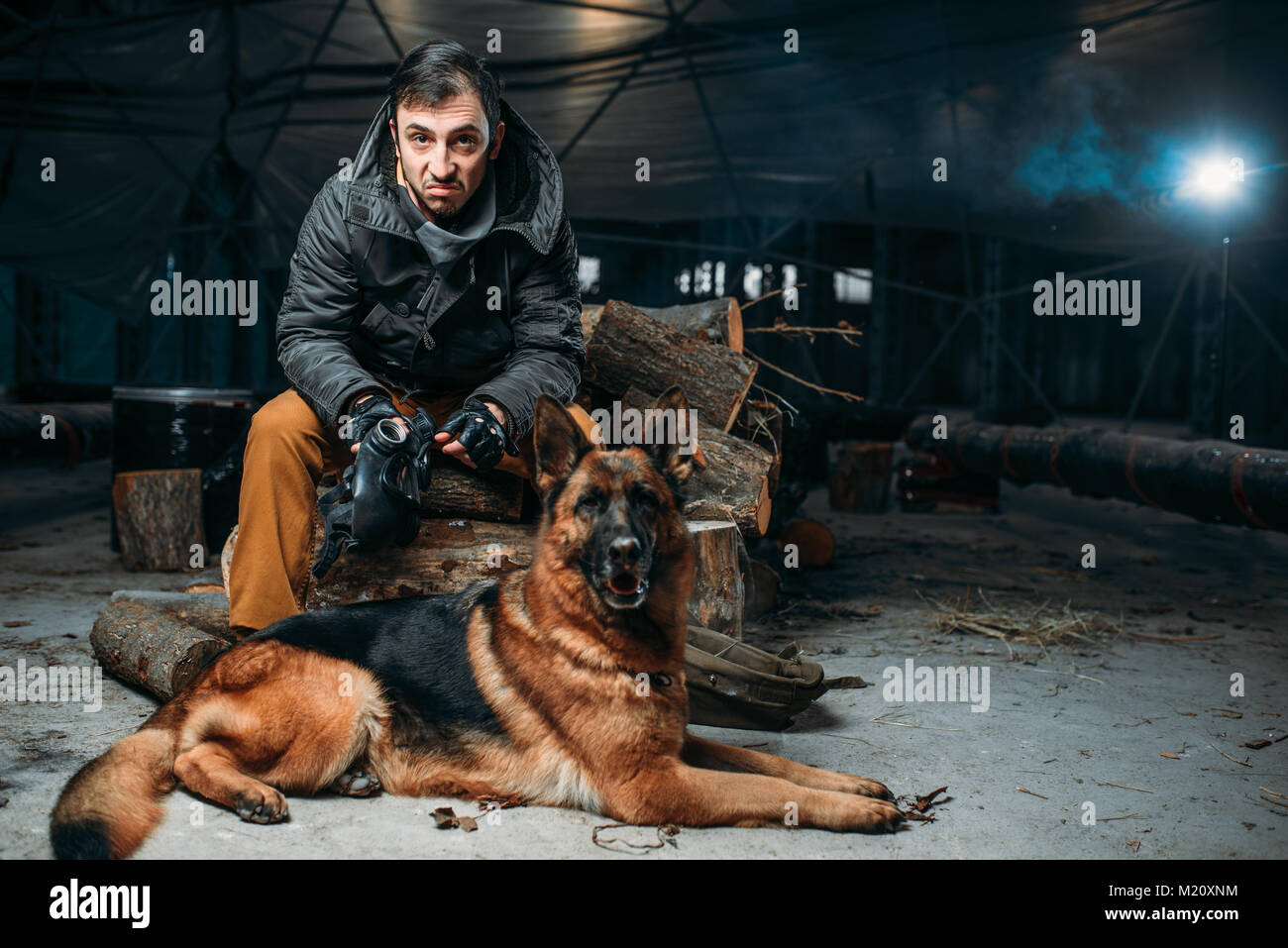Stalker and dog, friends in post apocalyptic world. Post-apocalypse lifestyle on ruins, doomsday, judgment day - Stock Image