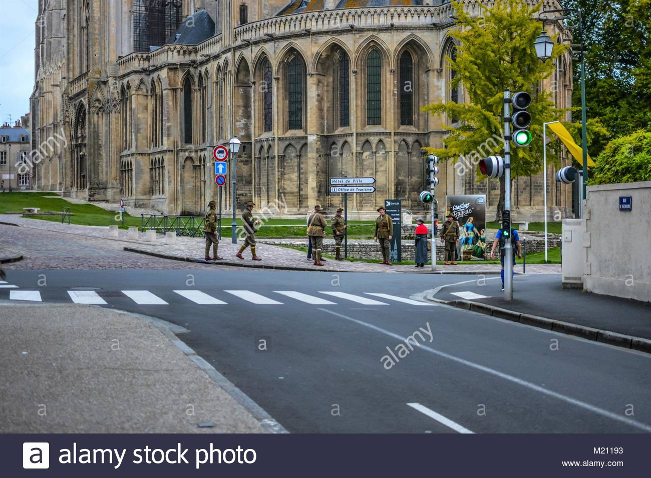 Men dressed in vintage World War soldiers' uniforms walk outside the Bayeux Cathedral in the historic Normandy town - Stock Photo