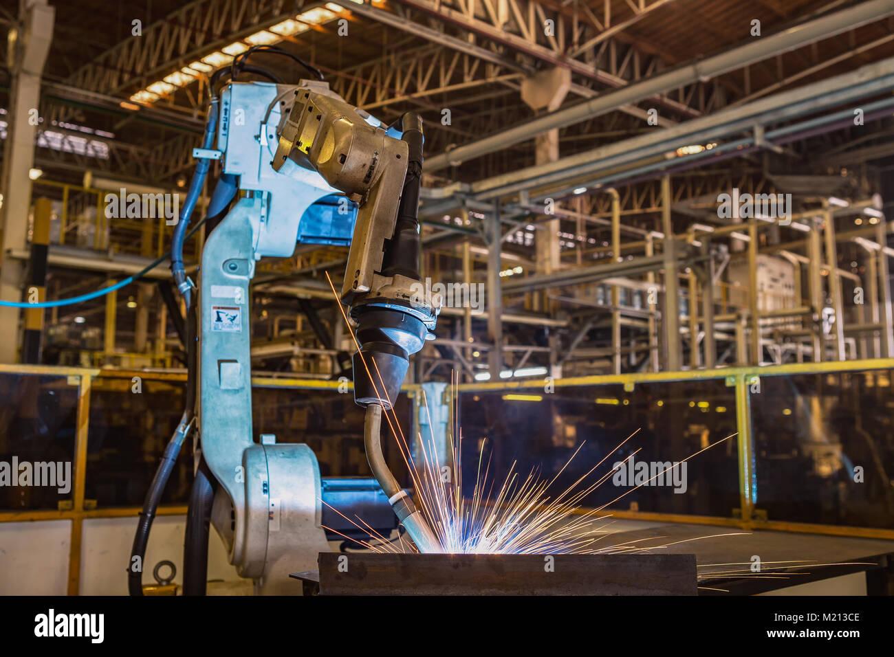 Robot is welding metal part in factory - Stock Image