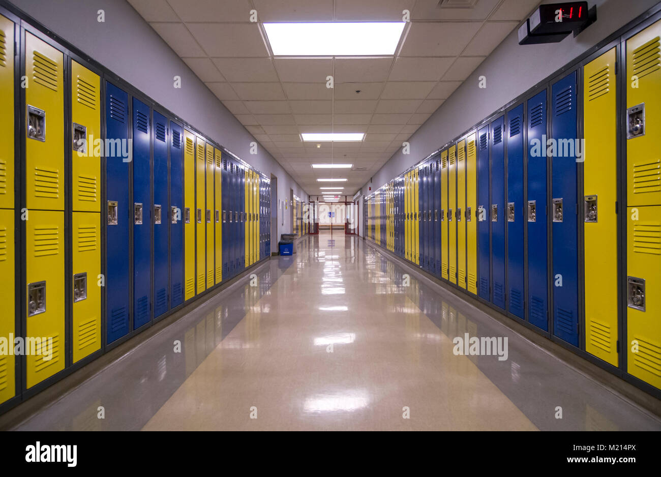 Symmetrical view of a school hallway with lockers on each side. - Stock Image