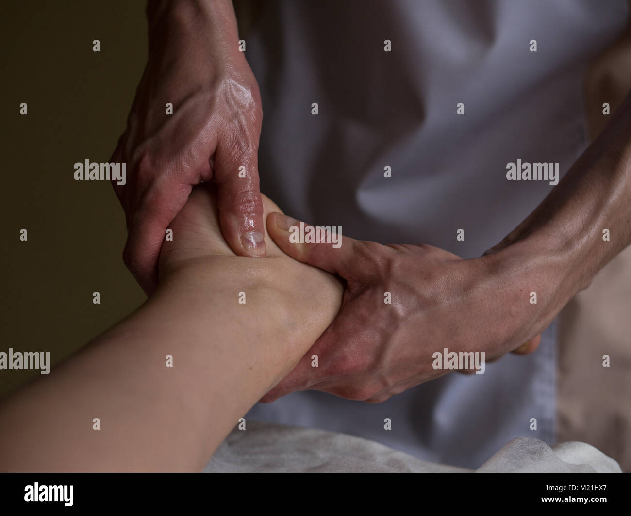 Beautiful young woman reciving relxing Foot Massage from Professional Masseur - Stock Image