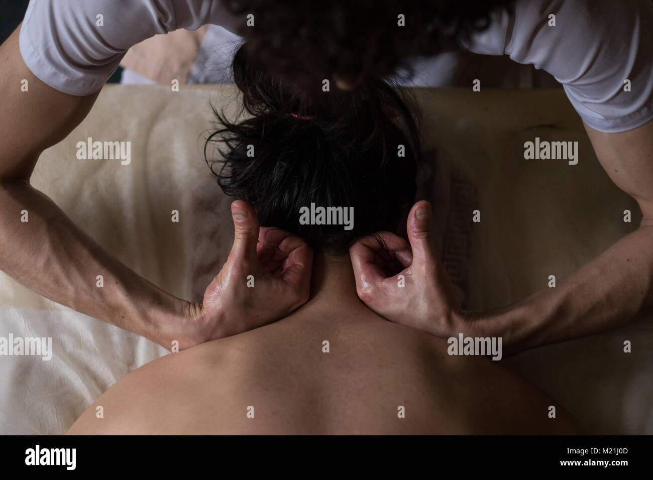 Beautiful young woman reciving relxing Massage of Her Oiled Neck from Professional Masseur - Stock Image