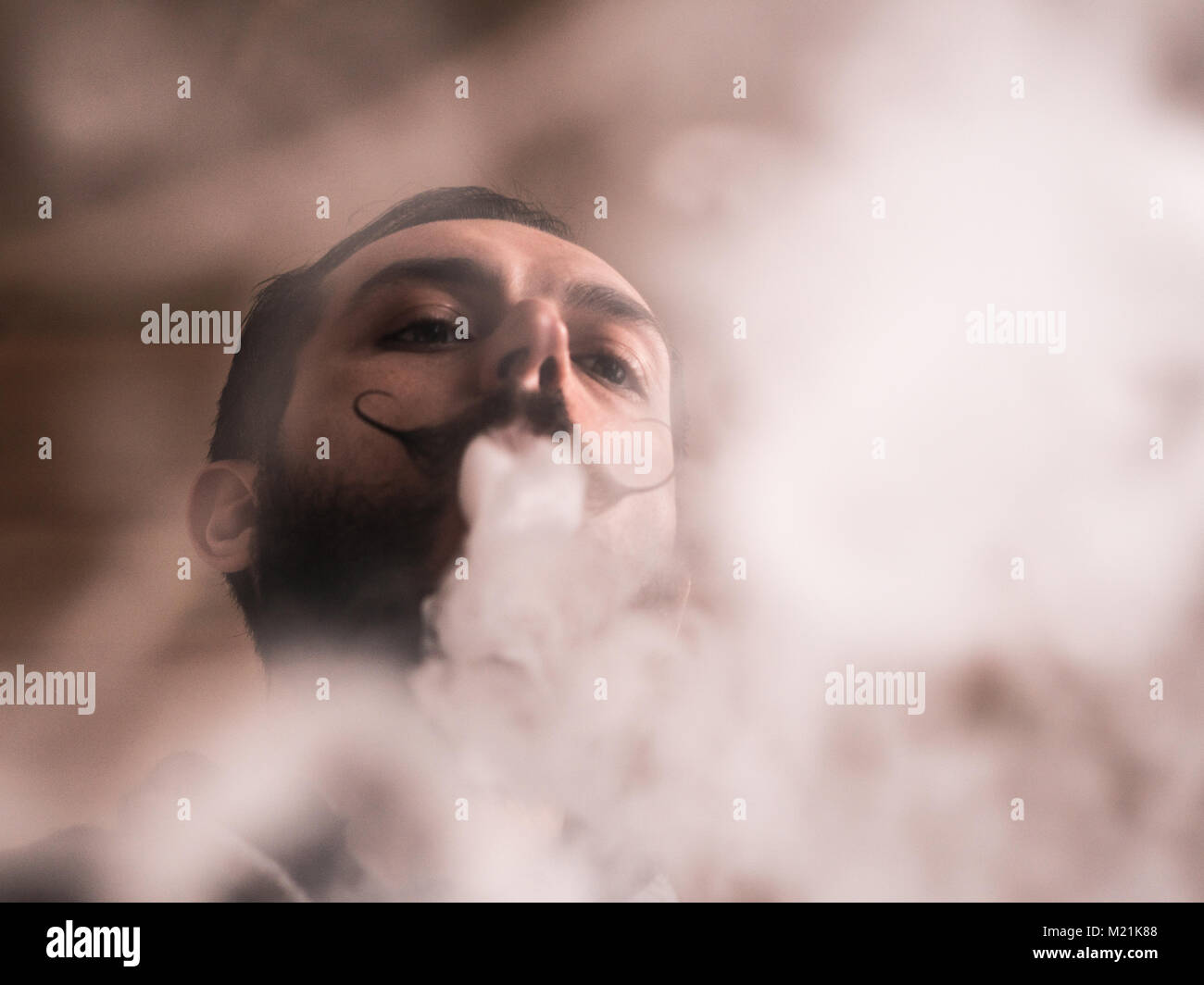 Man with Beard and Mustages Vaping an Electronic Cigarette. Vaper Hipster Smoke Vaporizer and Exhals Tight Smoke. - Stock Image