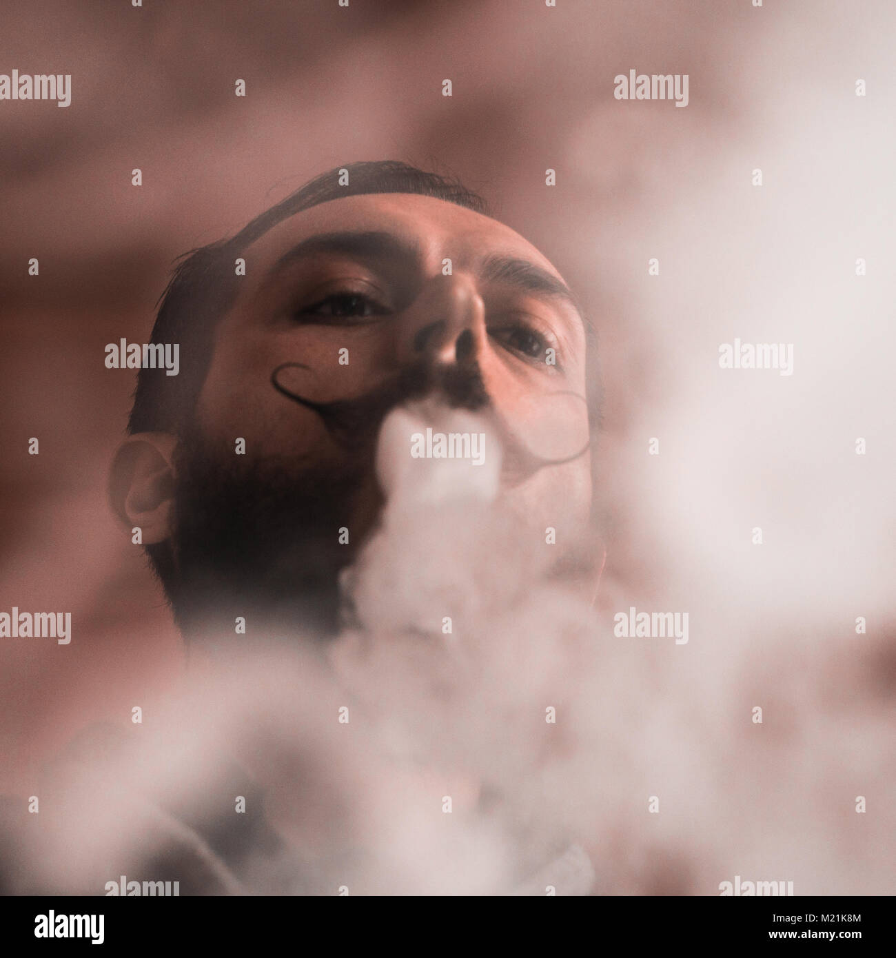 Man with Beard and Mustages Vaping an Electronic Cigarette. Vaper Hipster Smoke Vaporizer and Exhals Smoke Rings. - Stock Image