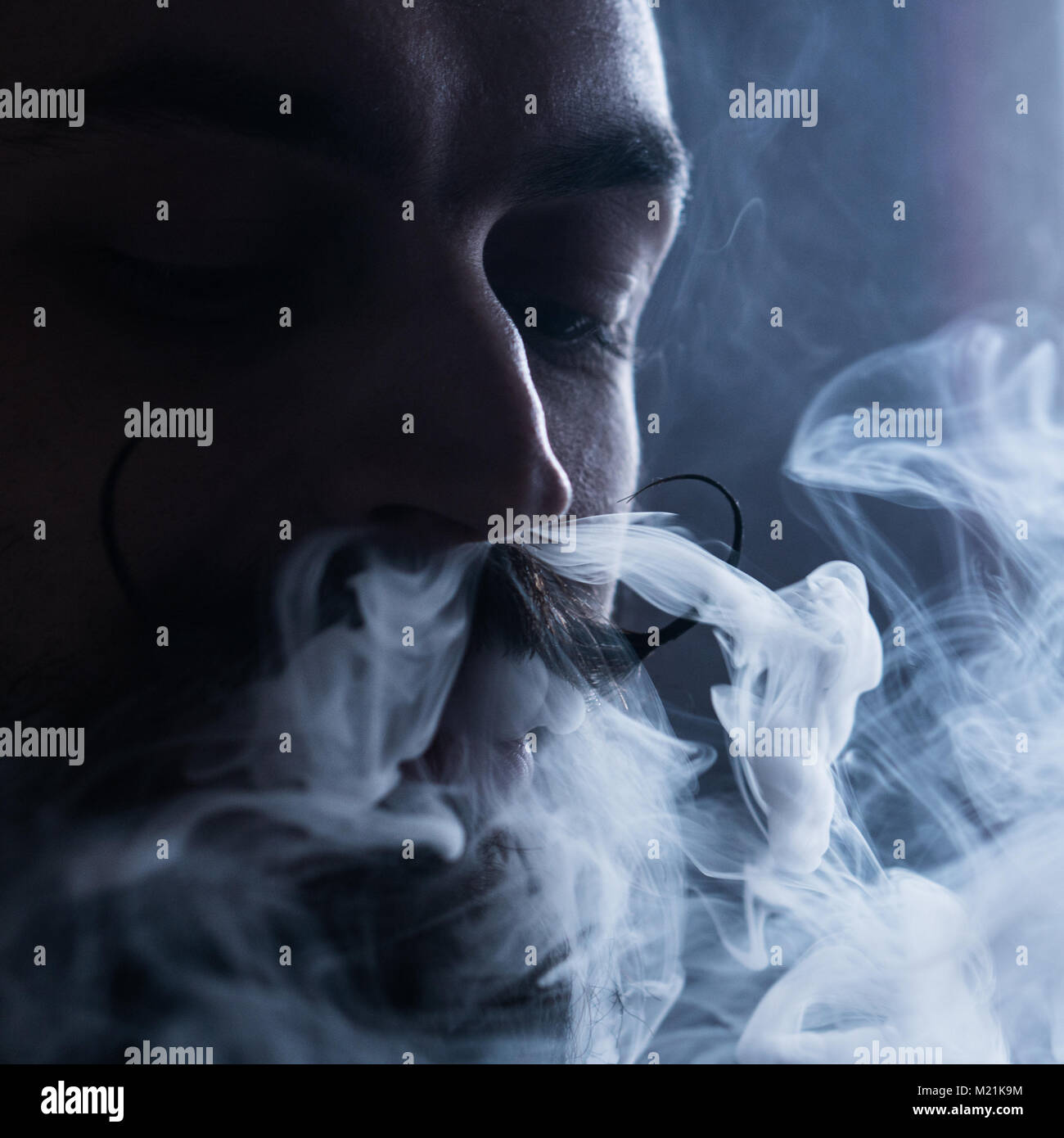 Man with Beard and Mustages Vaping an Electronic Cigarette. Vaper Hipster Smoke Vaporizer and Exhals Smoke Flow - Stock Image