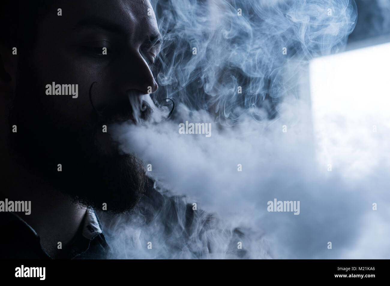 Man with Beard and Mustages Vaping an Electronic Cigarette. Vaper Hipster Smoke Vaporizer and Exhals Smoke Flow. - Stock Image