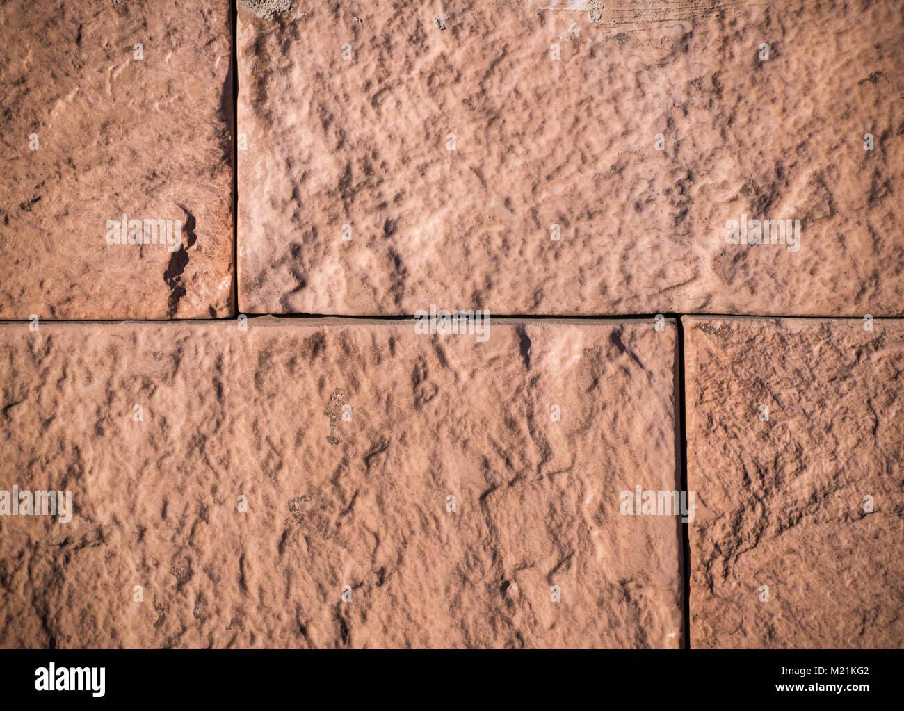 orange sandstone tiled wall. vignette; texture, background. - Stock Image