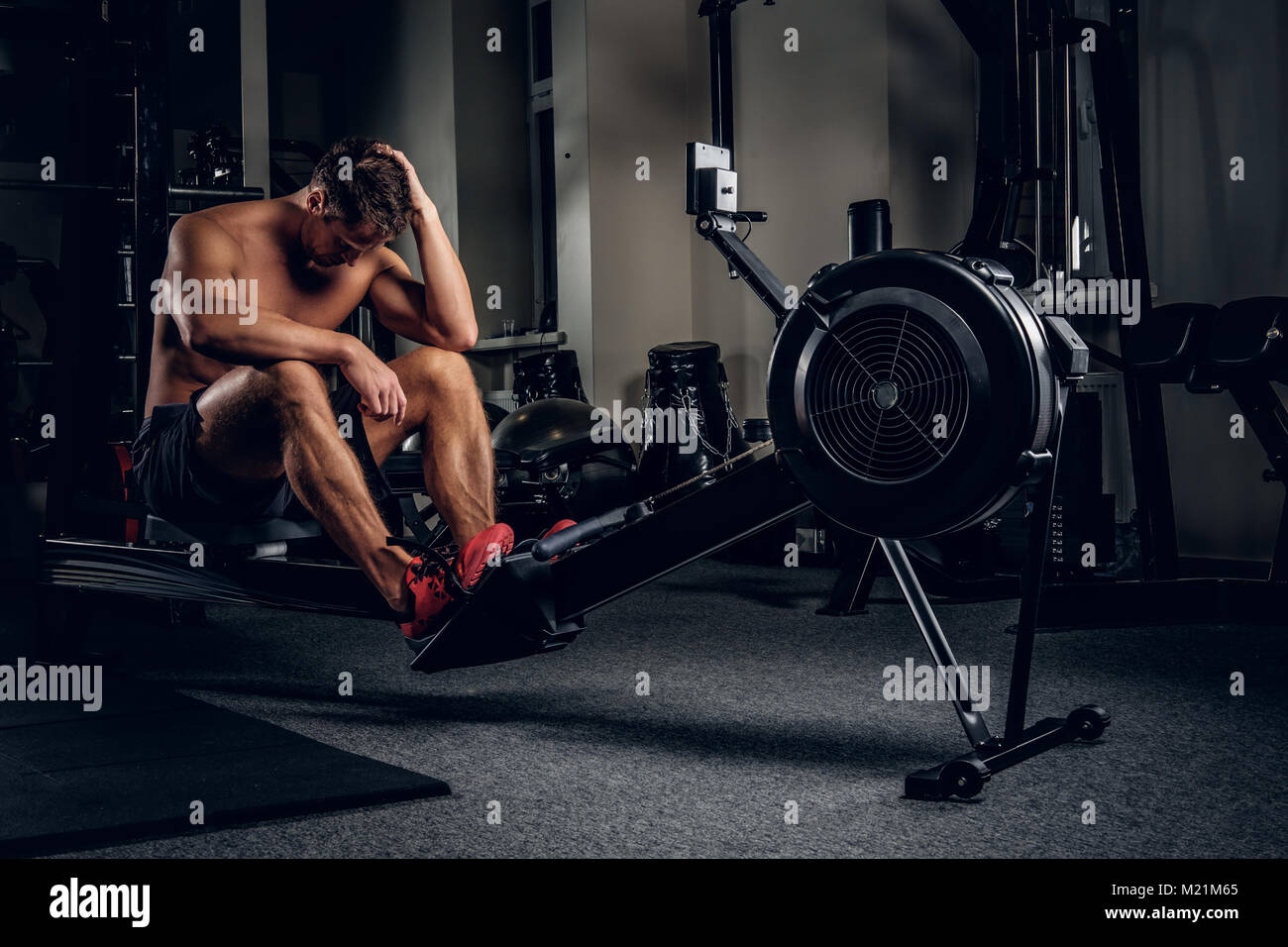 Tired sporty male after workouts on power exercise machine. - Stock Image