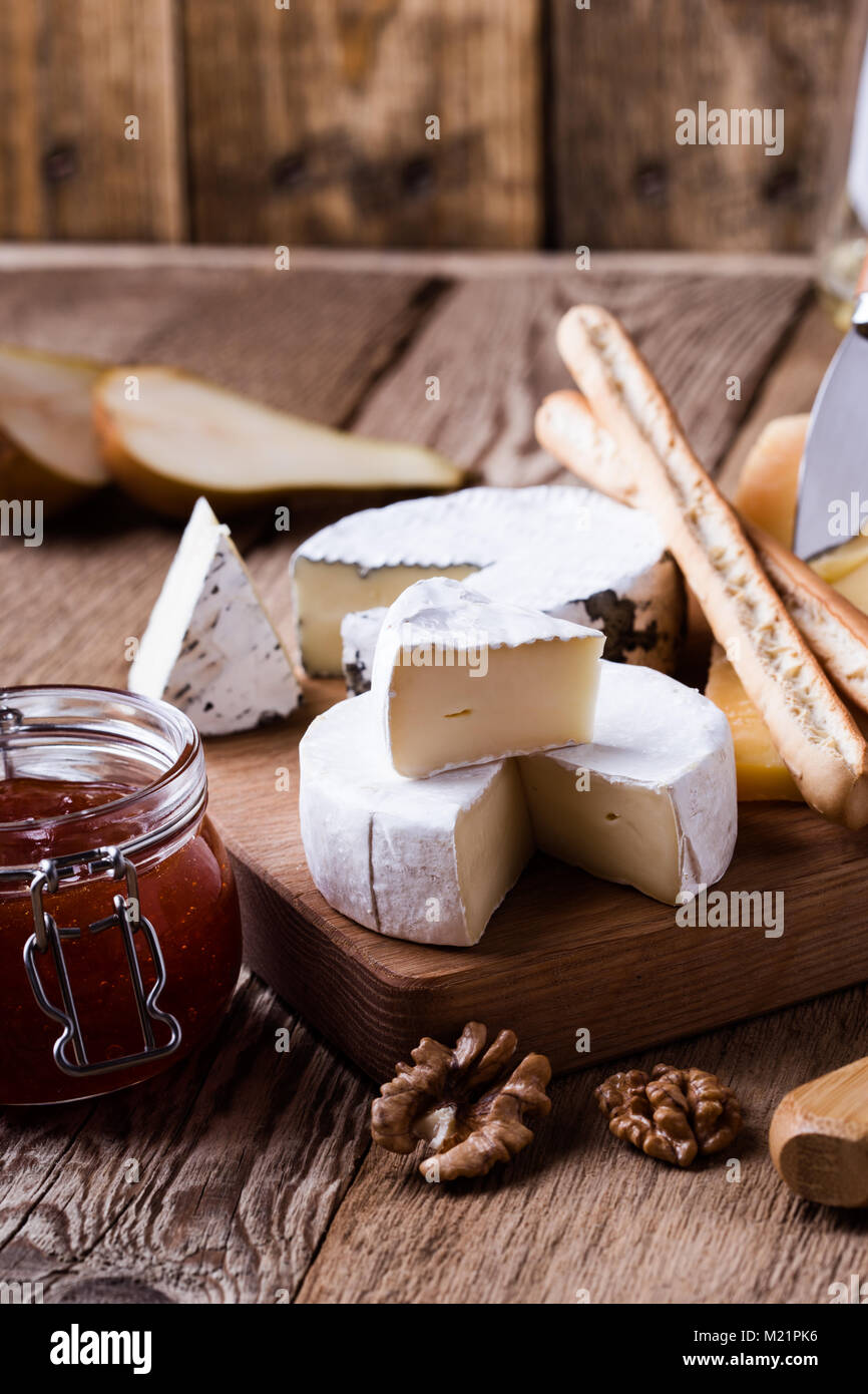 Board with different kinds of cheese on rustic wooden table - Stock Image